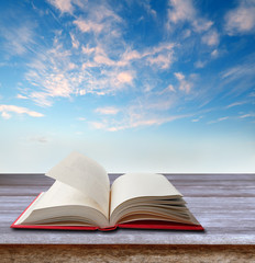 Open book on table and sky