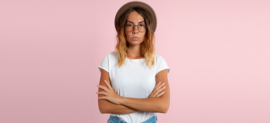 young woman posing on pink background wearing eyeglasses and hat
