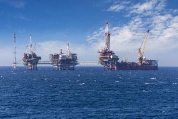 Big offshore oil rig drilling platform complex with anchored ship