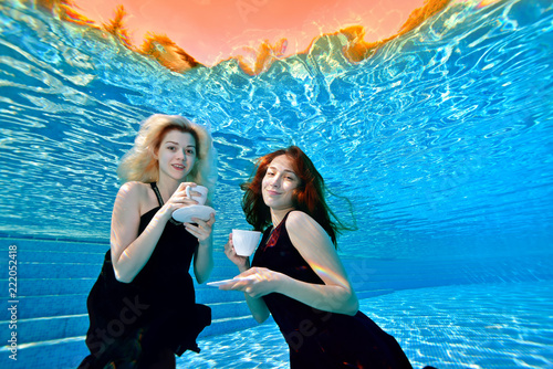 358f618c8 Two charming young girls swimming and posing underwater in the pool ...