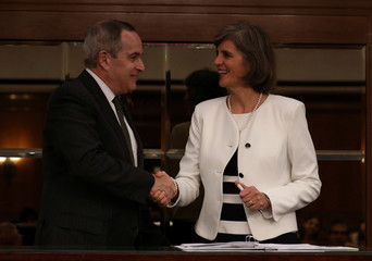 Decio Oddone, chief of Brazil's oil regulator ANP and Carla Lacerda, president of ExxonMobil Brasil shake hands during the contracts signing ceremony with oil companies after the 15th round of oil field auctions, in Rio de Janeiro