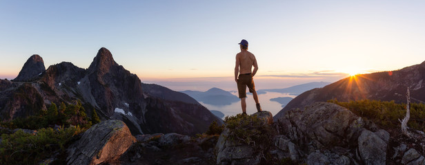 Man on top of a mountain enjoying the beautiful view during a vibrant summer sunset. Taken in Howe...