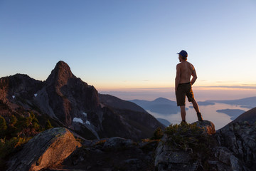 Man on top of a mountain enjoying the beautiful view during a vibrant summer sunset. Taken in Howe Sound, near Vancouver, BC, Canada.