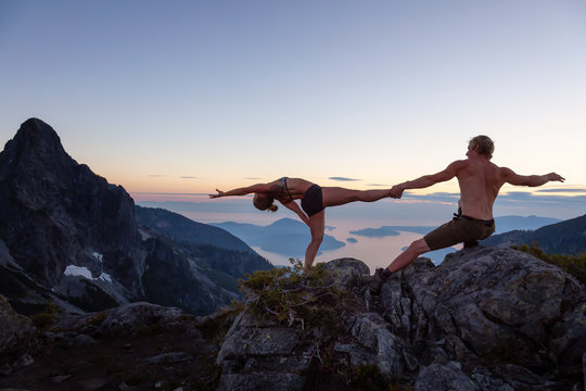 Man and Woman doing acroyoga on top of a mountain during a vibrant summer sunset. Taken in Howe Sound, near Vancouver, BC, Canada.