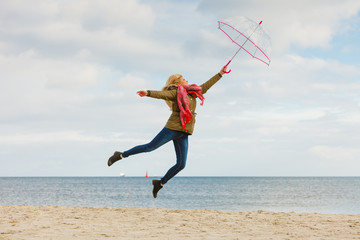 Woman jumping with transparent umbrella on beach
