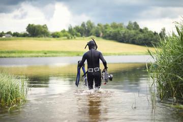 A scuba diver in a wet suit prepares