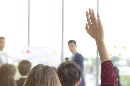 Female hand raised in university classroom, Interested man asking for questions in seminars.