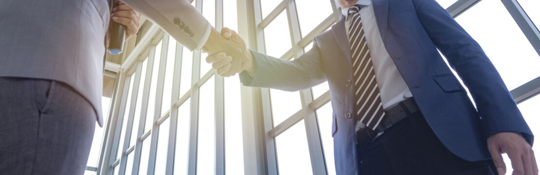 Two businessman handshake after taking about business deal that success together with all partnership, with under view from down point to top of handshake.