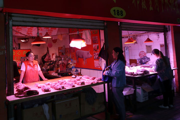 Customer visits a pork stall at a market on the outskirts of Harbin