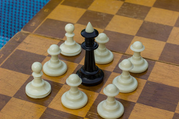 racism and intolerance concept of many white pawns chess figures person stay around one black king figure on wooden desk