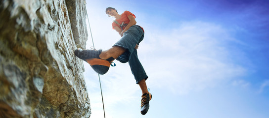 Photo sur cadre textile Alpinisme male rock climber on the cliff against a blue sky