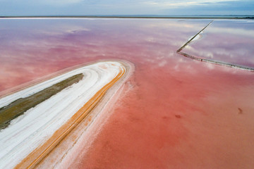 drone view to red salt lake with white shore