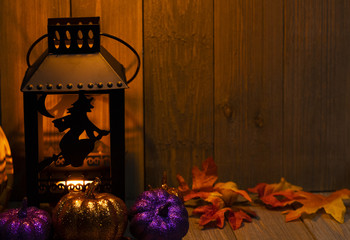 A witch lantern with pumpkins and fall maple leaves on a wooden background at night