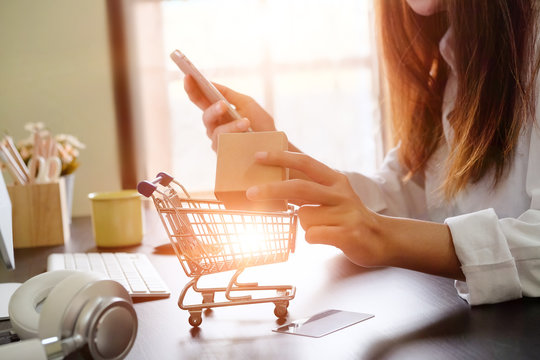 Boxes in a trolley with Woman hands, Shopping online concept.