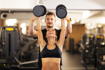 girl with fitness coach lifting weights