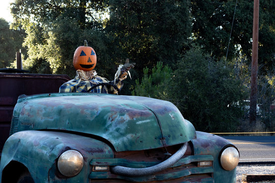 Smiling, happy, welcoming, fun friendly pumpkin head scarecrow driving an old truck to a halloween harvest party