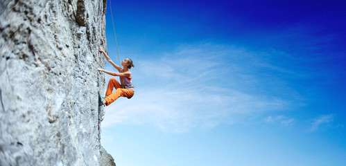 young slim woman rock climber climbing on the cliff