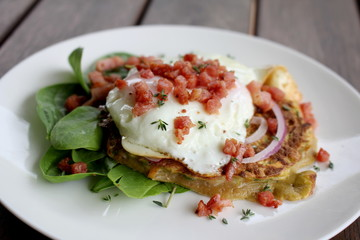 Zucchini and Sweet Potato Fritters with fried egg, bacon and salad, gourmet