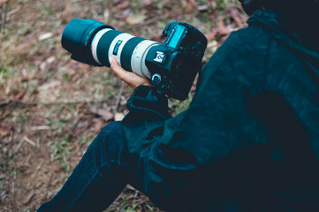 A photographer holds a camera, prepares a photograph of various tasks, and a camera with a lens he loves.