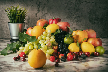 Still life of variery of fruits, oranges, grapes, strawberry, apples berries, cherry, lime and lemons on marble floor in vintage tone