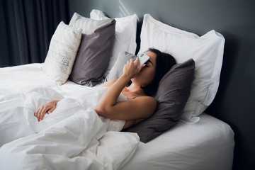 Tired girl sleeping in a bed. Fall asleep with the cell phone on her face. Facepalm gesture with a phone
