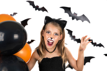 Smiley girl with black cat costume, halloween makeup and black and orange balloons at halloween party, pumpkin patch. Halloween kids.