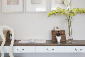 Wooden desk and chair decorate in home. Wooden drawer and vase on the desk.
