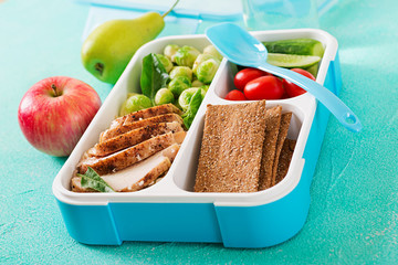 Healthy green meal prep containers with chicken fillet, rice, brussels sprouts and vegetables overhead shot with copy space. Dinner in lunch box.