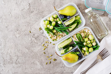 Vegan green meal prep containers with  rice, green beans,  brussel sprouts, cucumber and fruits. Dinner in lunch box. Top view. Flat lay