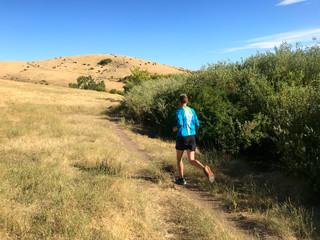 Man running up a grassy trail