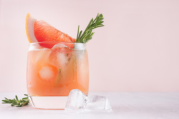 Cold grapefruit alcohol cocktail in misted glass with rosemary and grapefruits slice closeup on pastel fashion pink background.