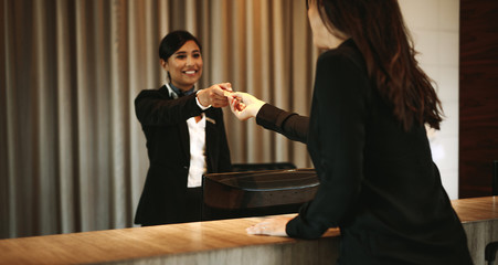 Female guest taking room key card at check-in desk
