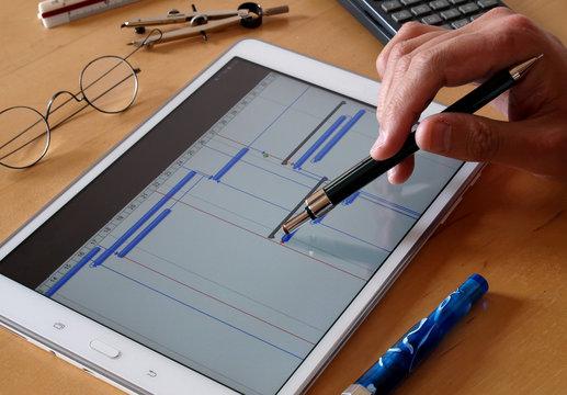 engineer working over timeline gantt progress chart of project on tablet computer screen