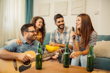 Group of happy friends having fun at home where they playing guitar, eating popcorn and drinking beer