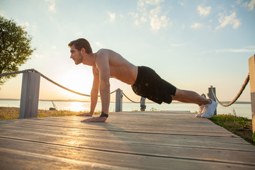 Picture of a young athletic man doing push ups outdoors