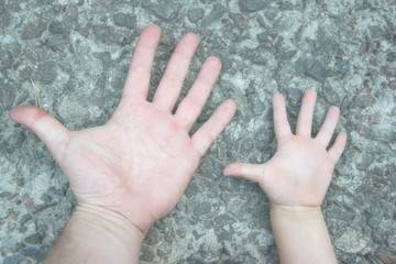 The hand of a man and a boy: father and son on the background of stones.