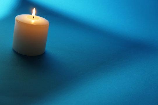 White candle burning on blue backgound