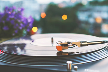 Vinyl player on a sunset background with a bokeh lights of the evening city. The needle on a rotating black vinyl plate. Included gramophone and rotating plate. Stylus with a needle close-up