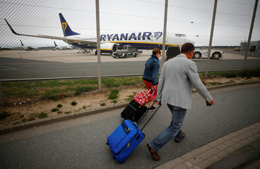Passengers walk in front of an aircraft of low-cost airline Ryanair at Weeze Airport