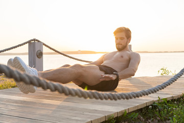 A shot of an athlete doing sit-ups outside.