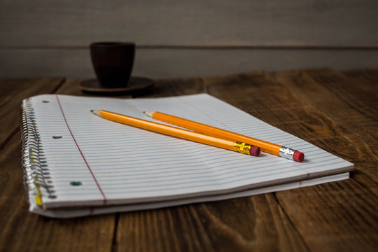 a notepad with pencils and cup of tea on wooden background