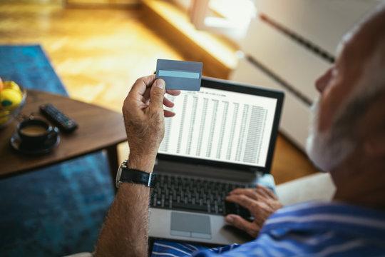 Senior man doing online shopping while sitting at home