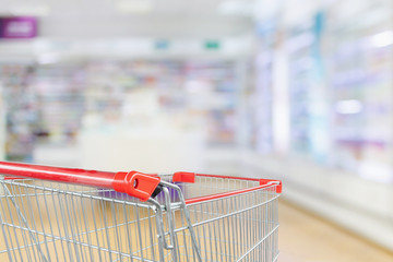 Empty red shopping cart with Pharmacy drugstore blur abstract backbround with medicine and healthcare product on shelves