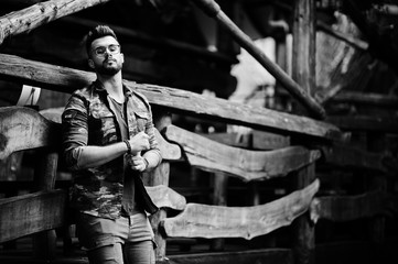 Awesome beautiful tall ararbian beard macho man in glasses and military jacket posed outdoor against wooden rustic house.