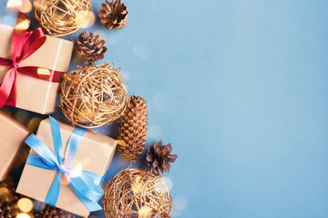 Christmas background with gift boxes and cones on blue background. Gift boxes tied with red and blue ribbons. Top view with copy space.