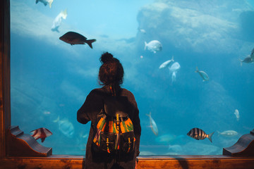 Young woman with backpack watches fish in a tank at an oceanarium