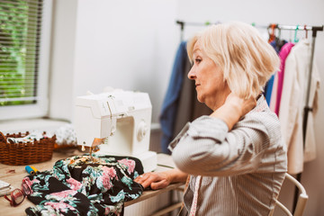 Adult woman is sewing in her studio. She is tired and having pain in her back.