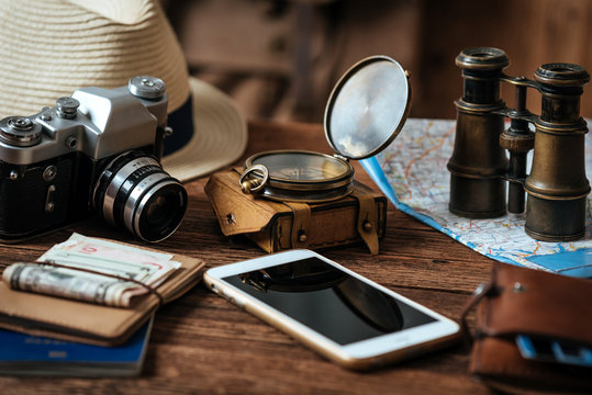 Mobile phone with blank screen on wooden table background. Looking image of traveling concept.