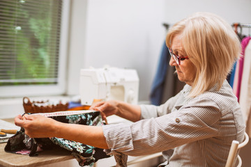Adult woman is sewing in her studio.