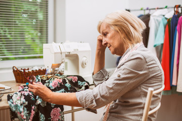 Adult woman is sewing in her studio. She is frustrated because she made a mistake.